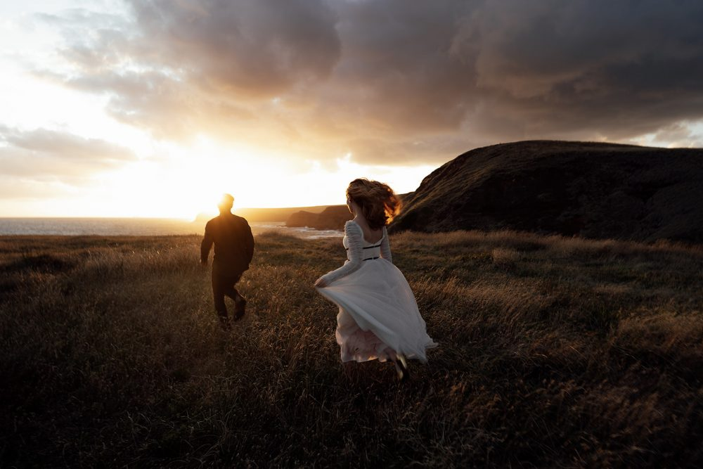 Wedding couple running in the field during sunset