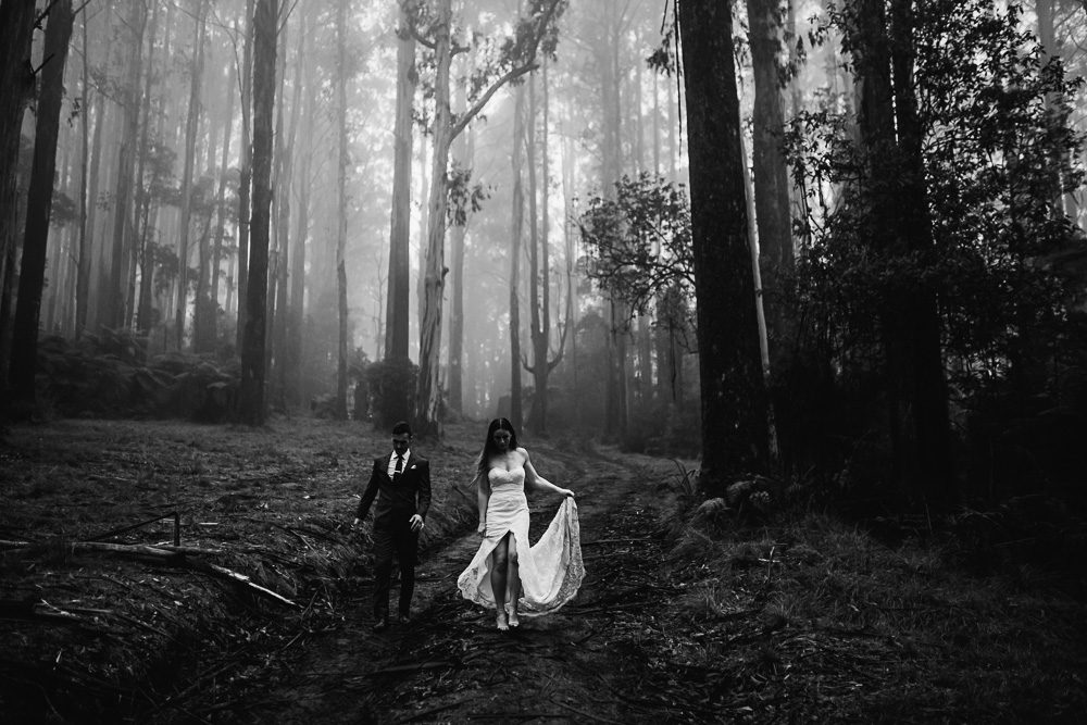 Black and white photo of wedding couple walking in the forest