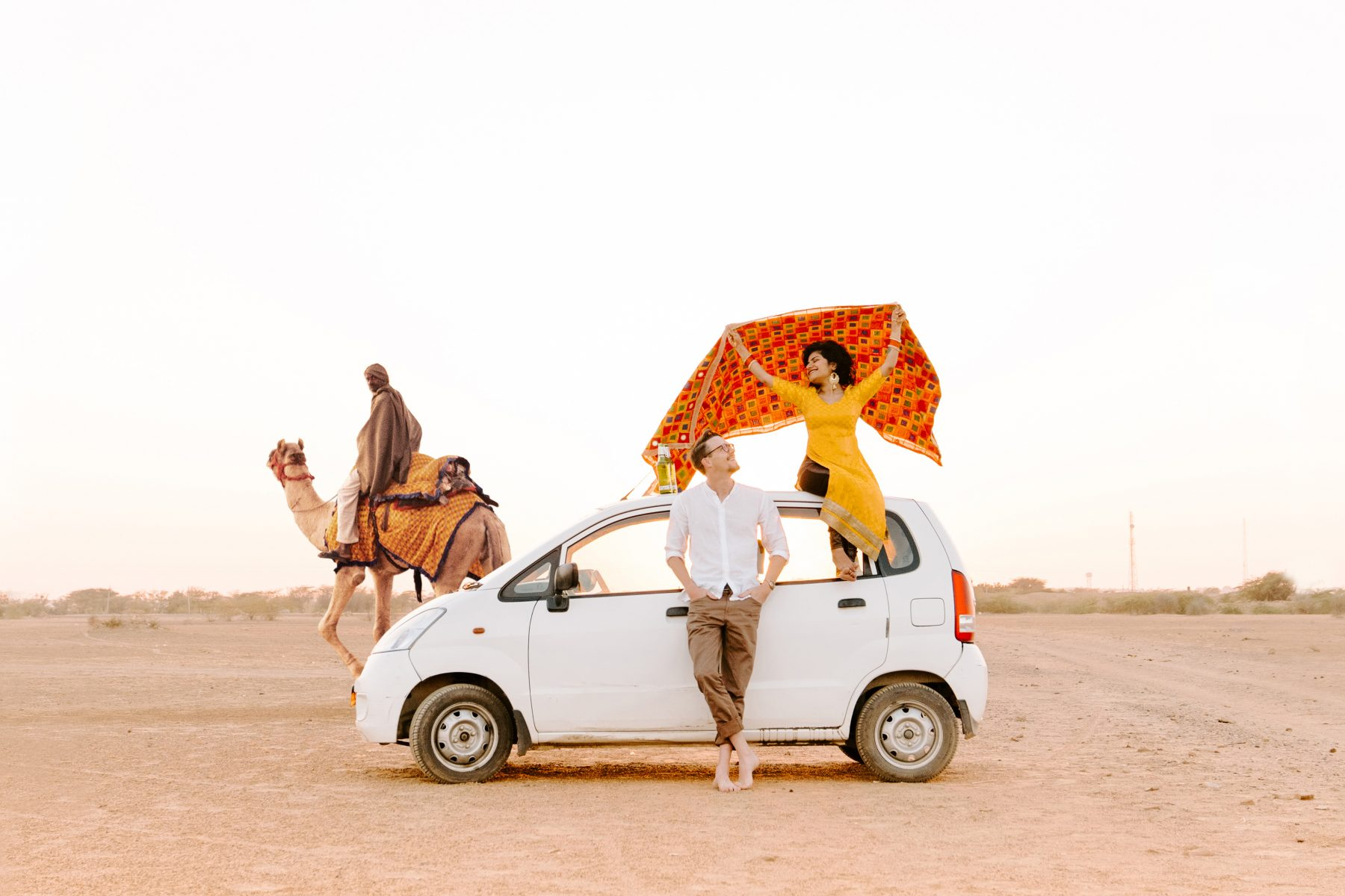 Man and woman leaning on a white car in the desert.
